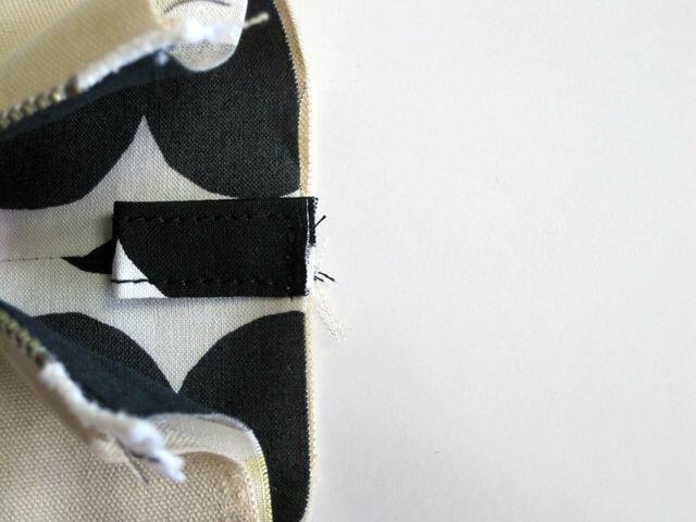 (14)幅1.5cmのタグを作ります。 表地の両サイドに5mm幅ステッチで縫いつけます。
